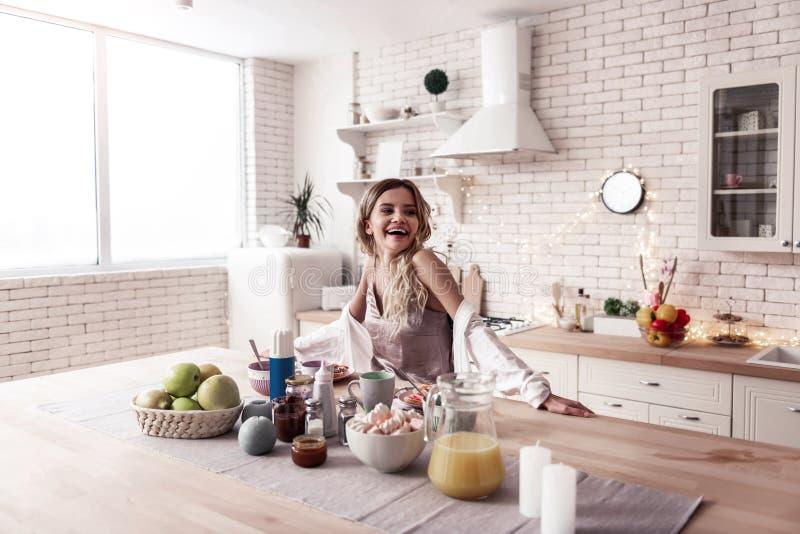 Jovem mulher de cabelos compridos bonita e seu marido de cabelo escuro que cozinham o café da manhã junto imagem de stock royalty free