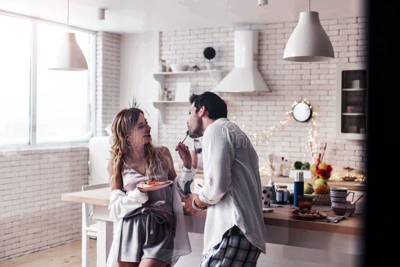 Jovem mulher de cabelos compridos bonita em uma parte superior do cetim que alimenta seu marido fotografia de stock royalty free