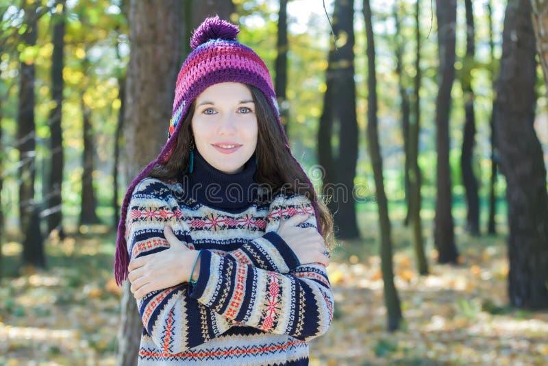 Jovem mulher de congelação que veste o chapéu felpudo feito malha e o abraço d foto de stock royalty free