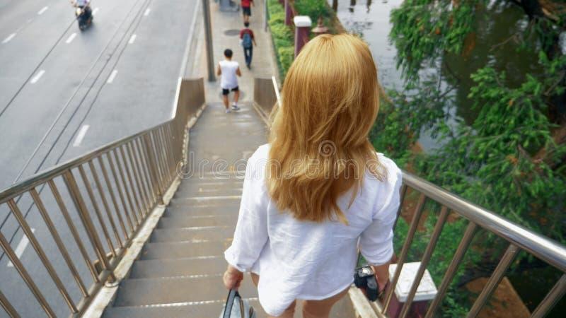 Jovem mulher de encantamento com o cabelo dourado, andando no centro da cidade, anda através da ponte imagens de stock