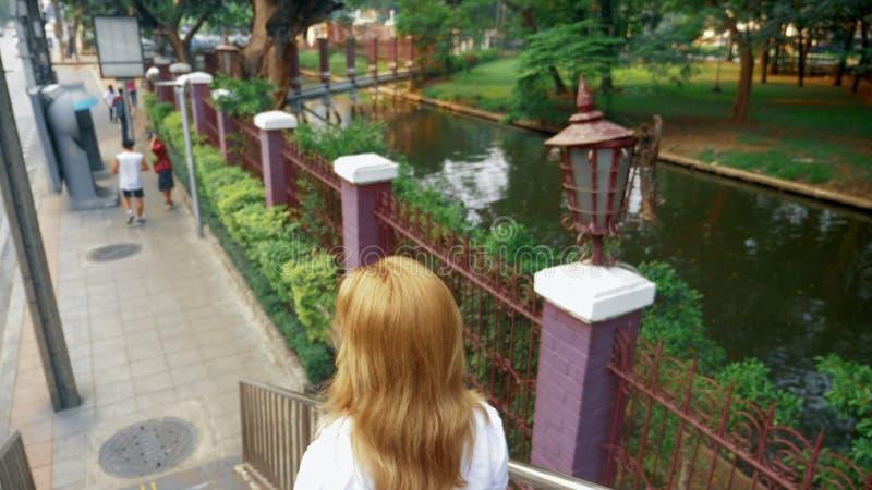 Jovem mulher de encantamento com o cabelo dourado, andando no centro da cidade, anda através da ponte foto de stock royalty free