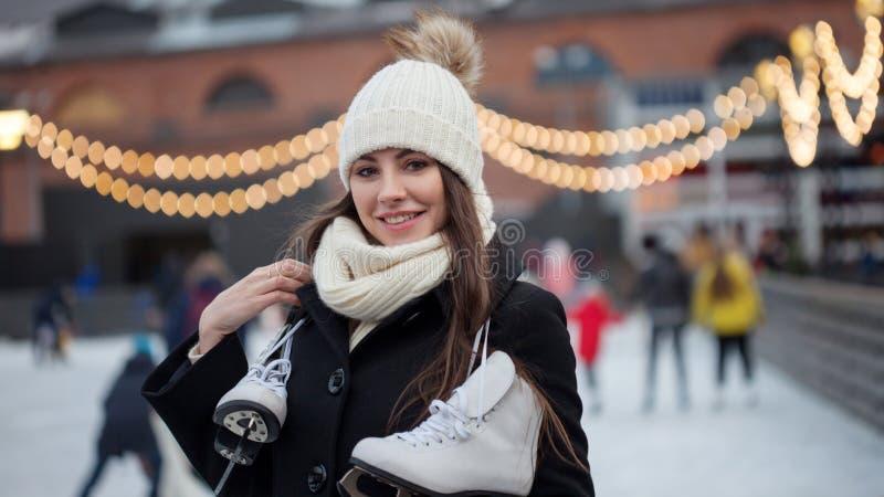 Jovem mulher de encantamento no parque perto da pista de gelo foto de stock