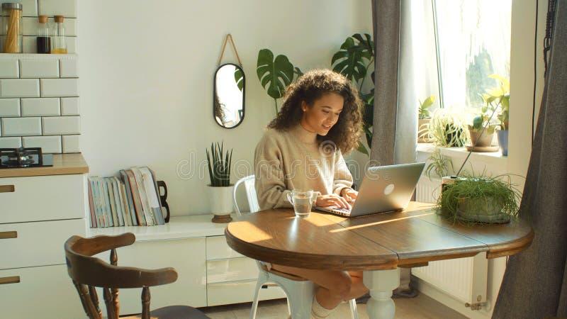 Jovem mulher de encantamento que datilografa no laptop em uma cozinha foto de stock royalty free