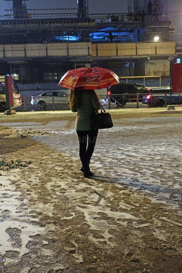 Jovem mulher de espera com o guarda-chuva na noite sob a neve de queda foto de stock royalty free