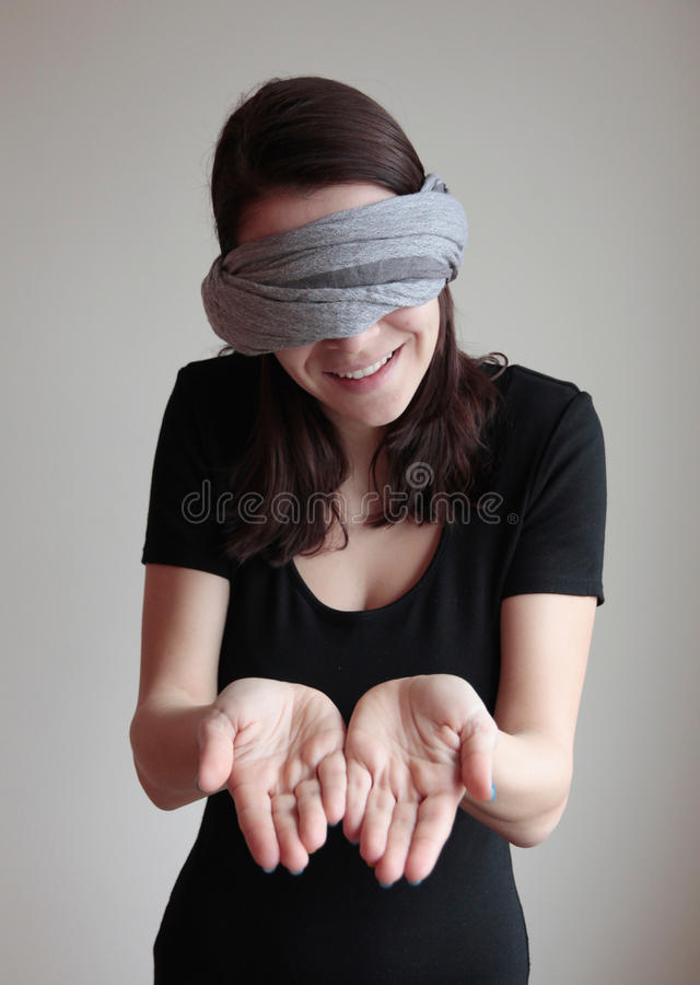 Jovem mulher de olhos vendados que mostra as palmas fotografia de stock