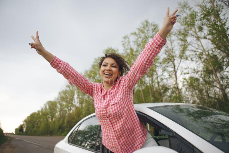 Jovem mulher de riso bonito que pendura para fora sua cabeça de um carro através da janela aberta que aprecia a liberdade da bris fotografia de stock royalty free