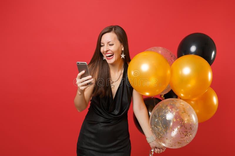 Jovem mulher de riso em pouco vestido preto que guarda balões e utilização de ar do telefone celular ao comemorar isolada no verm fotos de stock royalty free