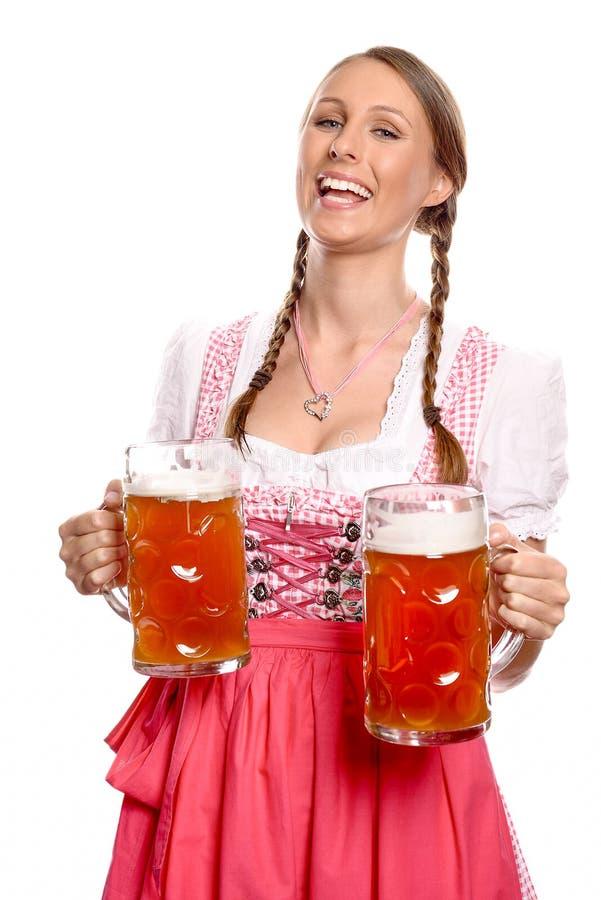 Jovem mulher de riso em uma cerveja do serviço do dirndl foto de stock