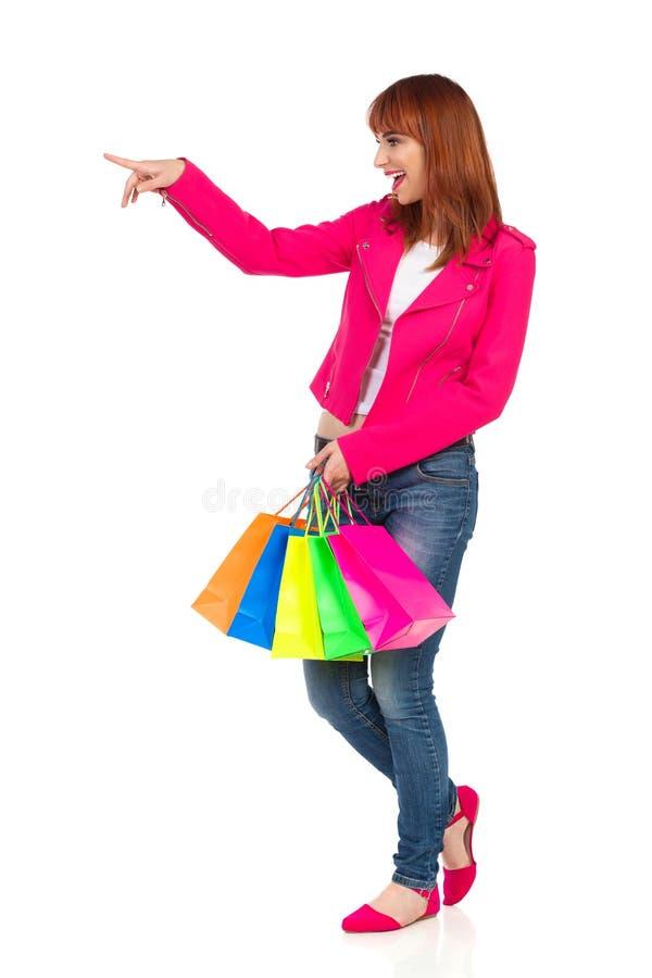 A jovem mulher de riso está levando sacos de compras, olhando ausente e apontar imagens de stock royalty free