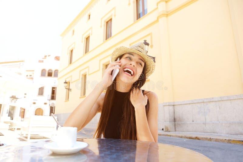 Jovem mulher de riso que aprecia a fala no telefone celular foto de stock