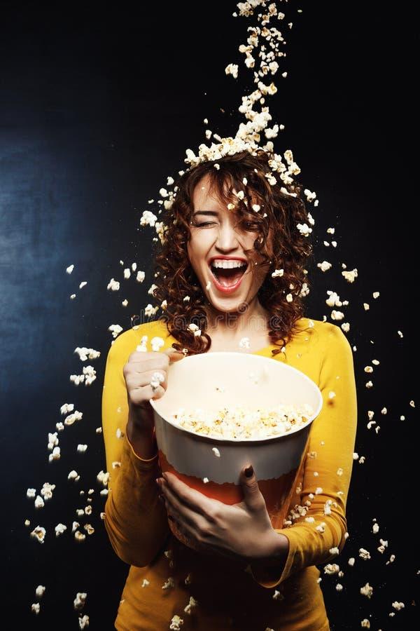 Jovem mulher de riso que fica sob o chuveiro de queijo da pipoca no cinema fotos de stock royalty free