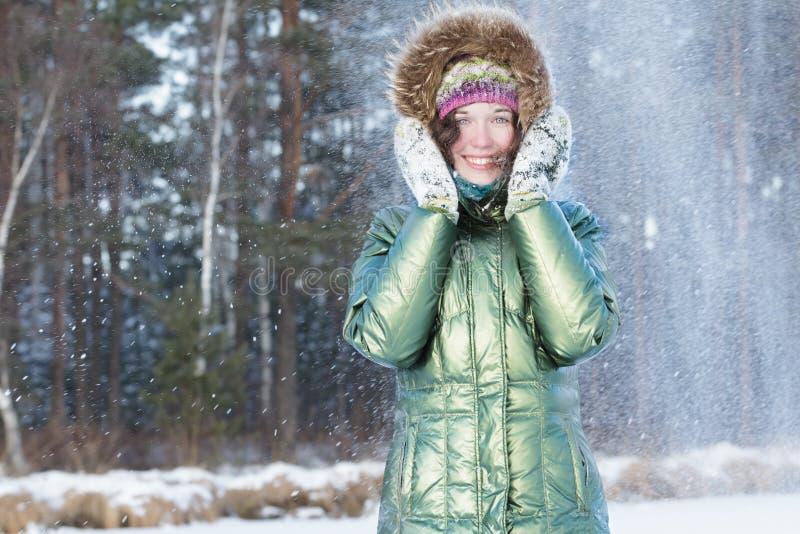 A jovem mulher de riso que guarda as mãos em mitenes felpudos aproxima a cara durante a tempestade de neve na floresta do inverno fotos de stock
