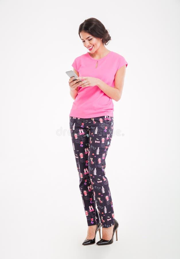 Jovem mulher de sorriso atrativa que está e que usa o telefone celular imagens de stock royalty free