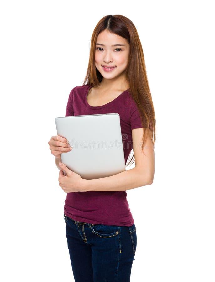Jovem mulher de sorriso atrativa que guarda o laptop imagem de stock