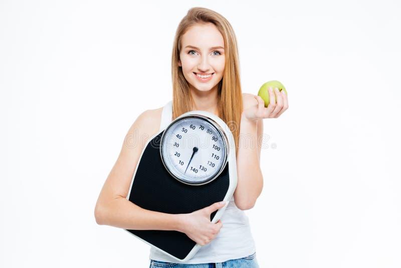 Jovem mulher de sorriso bonita com maçã e as escalas frescas fotografia de stock