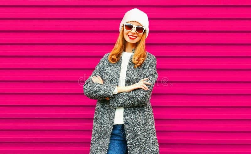 Jovem mulher de sorriso bonita com os braços cruzados no revestimento cinzento foto de stock