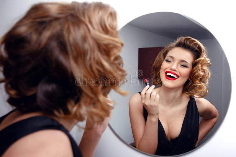 A jovem mulher de sorriso bonita com perfeito compõe, os bordos vermelhos, penteado retro no vestido preto, olhando no espelho foto de stock royalty free