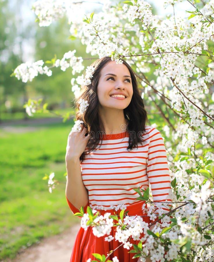 Jovem mulher de sorriso bonita do retrato que aprecia florescendo o jardim fotografia de stock