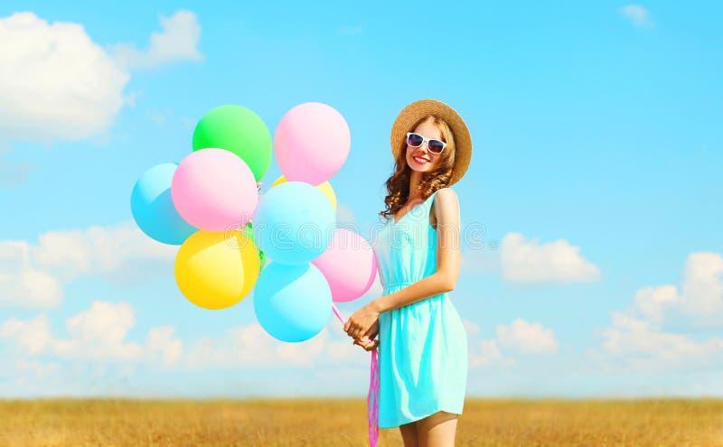 A jovem mulher de sorriso bonita feliz guarda balões coloridos de um ar que aprecia um dia de verão em um céu azul do prado fotos de stock royalty free