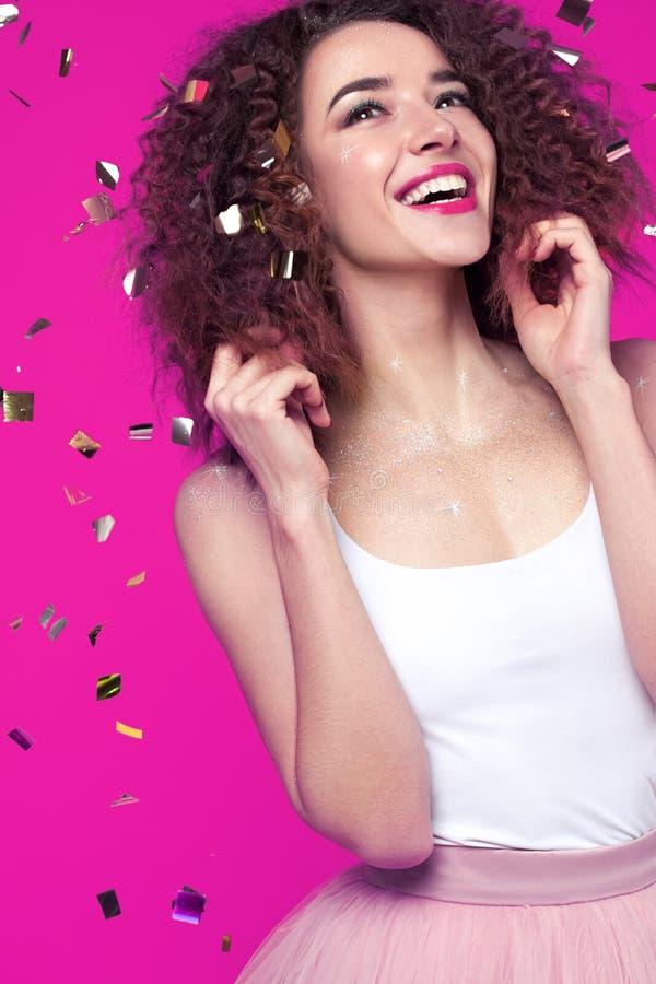 Jovem mulher de sorriso bonita no fundo cor-de-rosa com engodo do voo fotos de stock royalty free