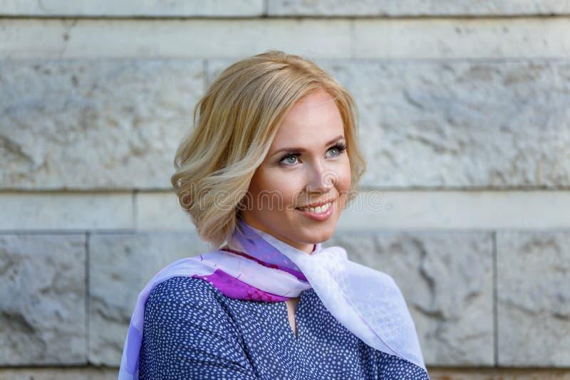 Jovem mulher de sorriso bonita perto da parede de pedra imagens de stock