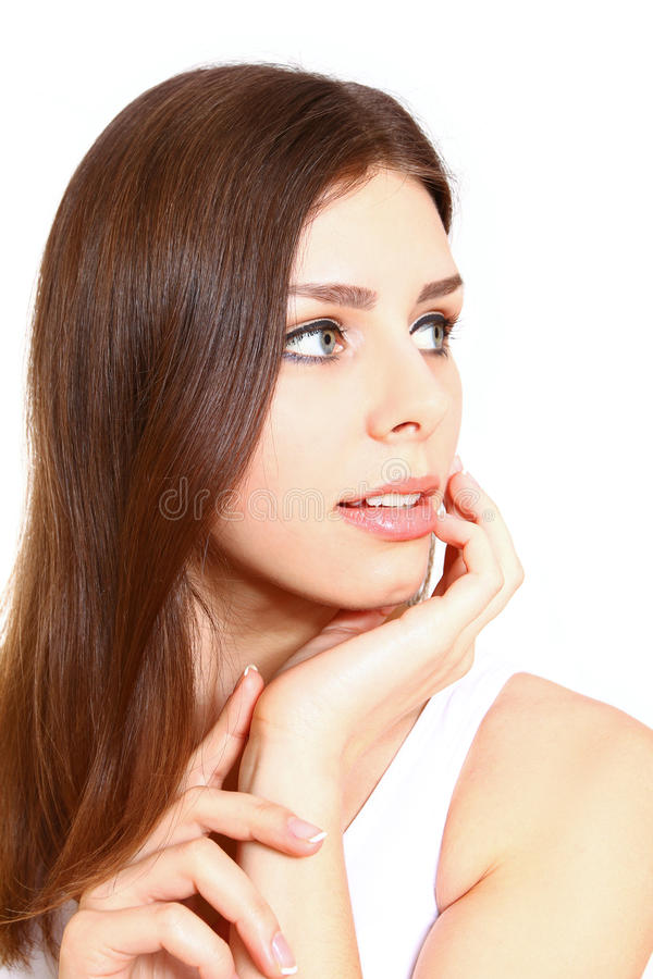 A jovem mulher de sorriso bonita que afaga sua cara limpa da beleza é fotos de stock royalty free
