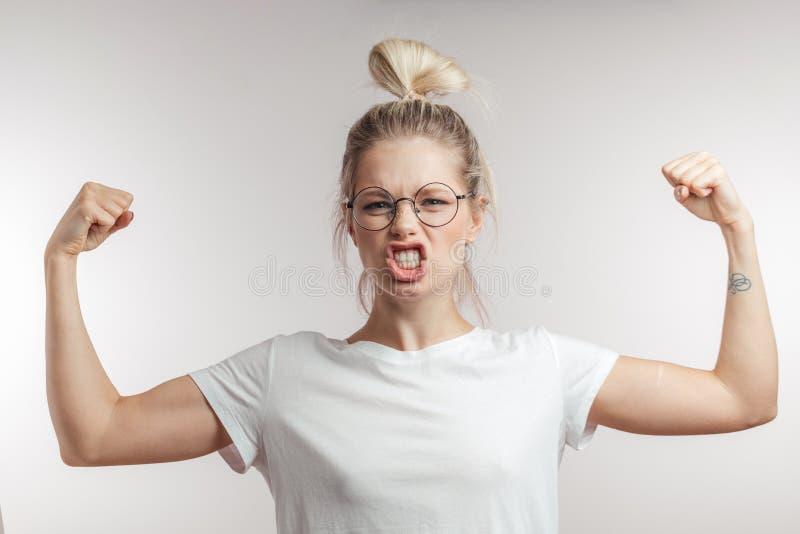 A jovem mulher de sorriso brilha dentro o t-shirt da pintura que dobra o bíceps, olhando a câmera imagens de stock