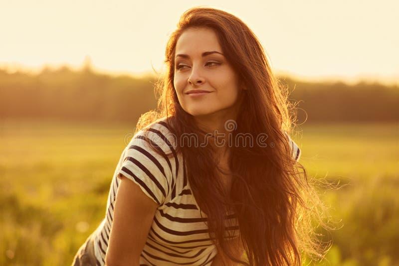Jovem mulher de sorriso calma bonita que olha feliz com cabelo longo brilhante longo no fundo brilhante do verão do por do sol da imagem de stock