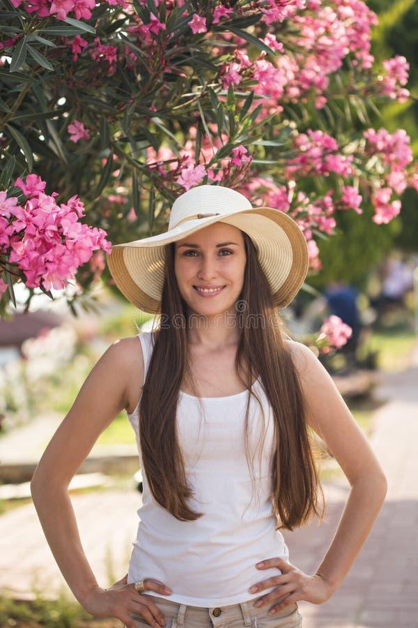 Jovem mulher de sorriso com as flores cor-de-rosa como o contexto fotos de stock