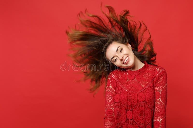 Jovem mulher de sorriso com cabelo de fluxo no vestido do laço que mantém a boca aberta, enganando isolado ao redor na parede ver imagem de stock royalty free