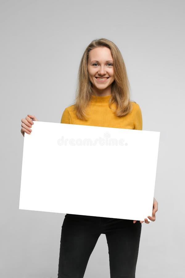Jovem mulher de sorriso com cartaz fotografia de stock