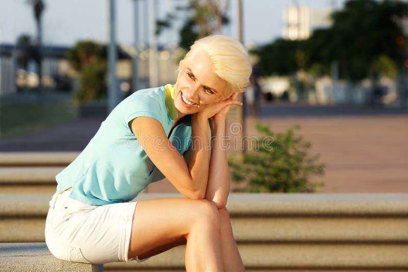 Jovem mulher de sorriso com o cabelo louro curto que senta-se fora imagem de stock