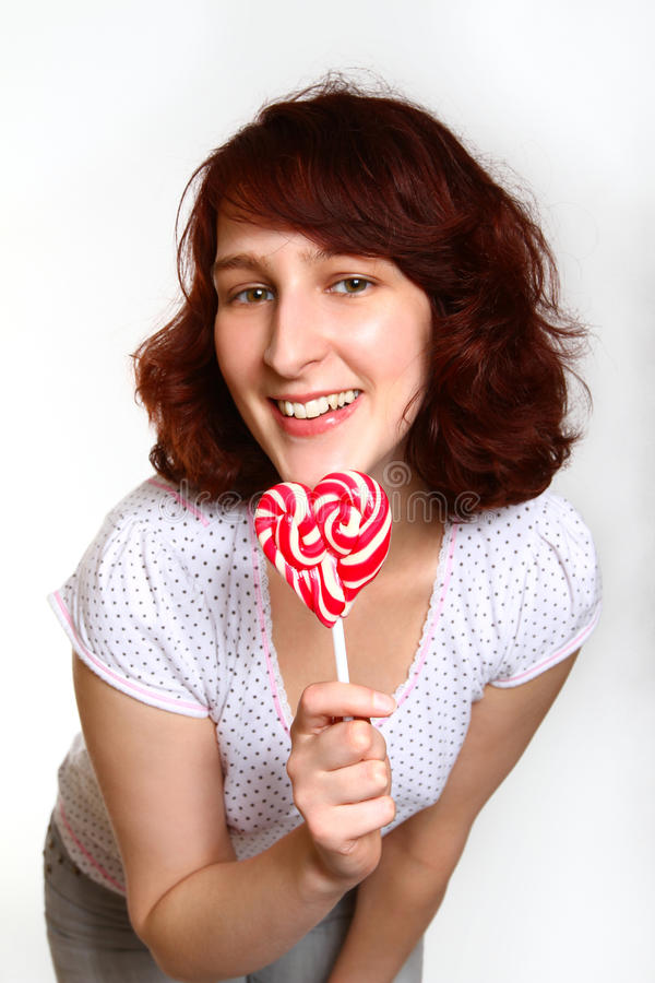 Jovem mulher de sorriso com o pirulito no fundo branco imagem de stock royalty free
