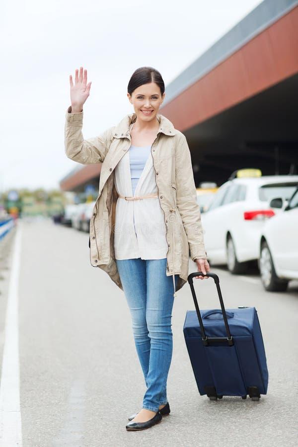 Jovem mulher de sorriso com o saco do curso sobre o táxi foto de stock royalty free