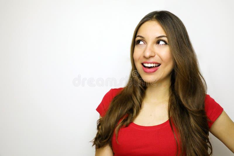Jovem mulher de sorriso com o t-shirt vermelho que olha ao lado no fundo branco Copie o espaço fotografia de stock royalty free