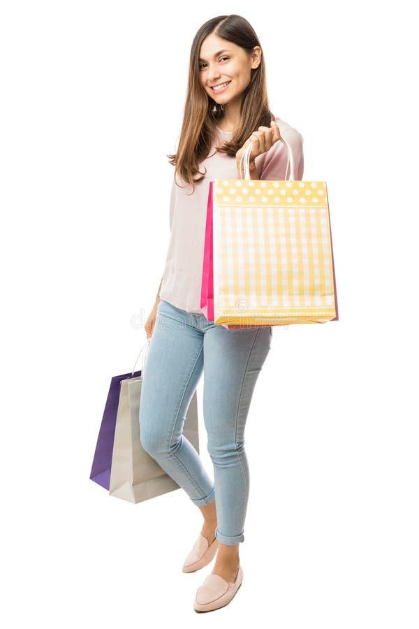 Jovem mulher de sorriso com os sacos de compras no fundo branco fotos de stock royalty free