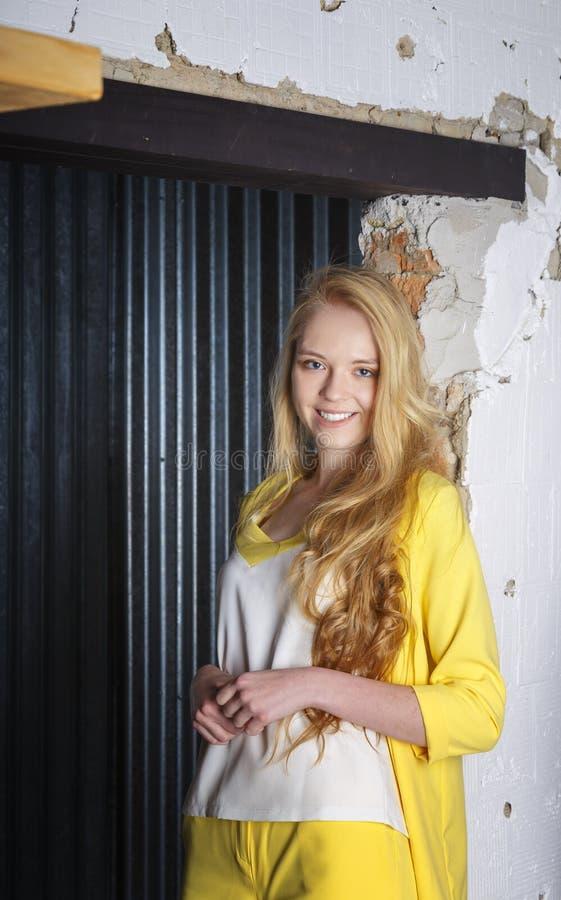 A jovem mulher de sorriso com suportes ondulados do cabelo louro da molva inclinou sua parte traseira contra a parede fotografia de stock royalty free