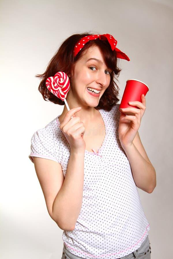 Jovem mulher de sorriso com um pirulito e um copo que levantam sobre imagens de stock royalty free