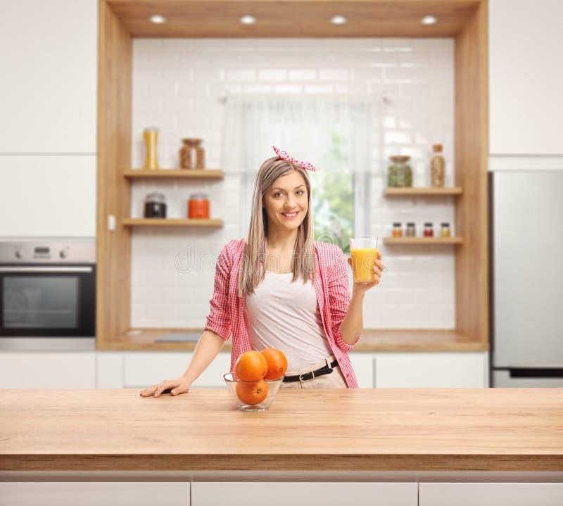 Jovem mulher de sorriso com um vidro do suco de laranja fresco atrás de um contador de madeira em uma cozinha moderna fotos de stock