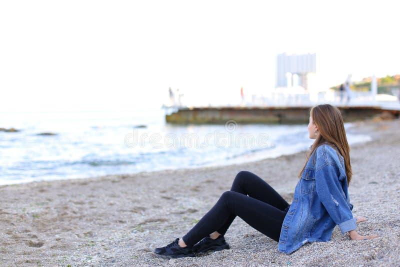 A jovem mulher de sorriso descansa na praia e nas poses in camera, sentando-se fotografia de stock