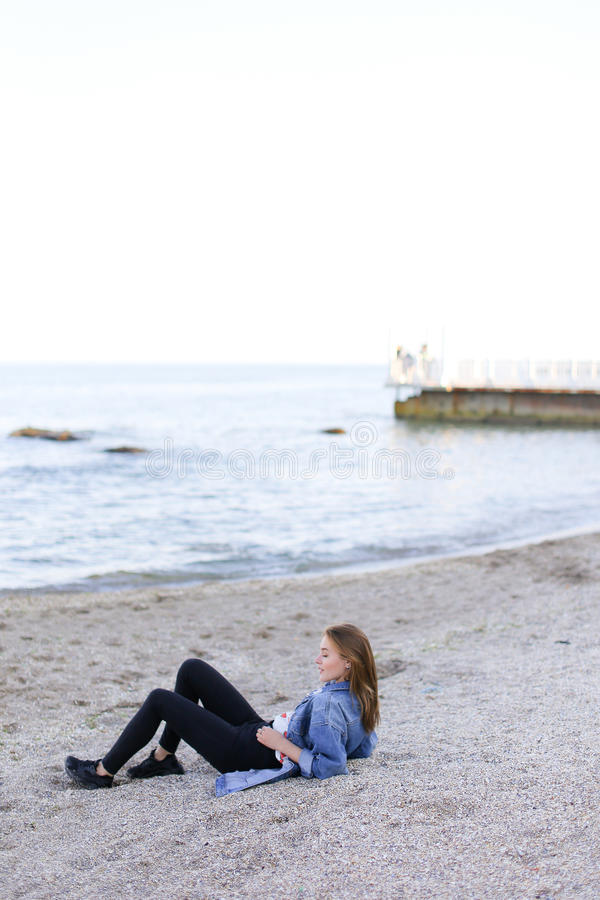 A jovem mulher de sorriso descansa na praia e nas poses in camera, sentando-se fotos de stock