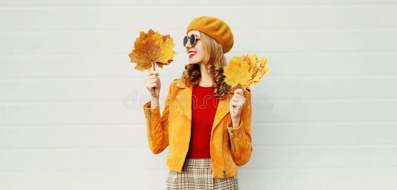 Jovem mulher de sorriso do retrato do outono que olha nas folhas de bordo amarelas na rua da cidade sobre a parede cinzenta foto de stock royalty free