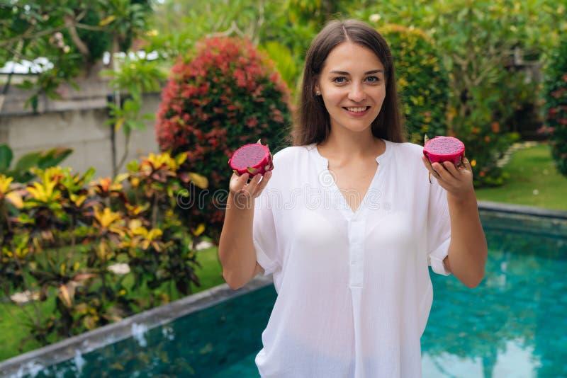 Jovem mulher de sorriso do retrato que guarda dois frutos do dragão, pitaya em suas mãos perto da associação imagens de stock