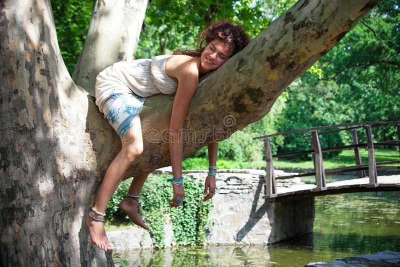 Jovem mulher de sorriso engraçada que relaxa na árvore no dia de verão do parque imagens de stock royalty free