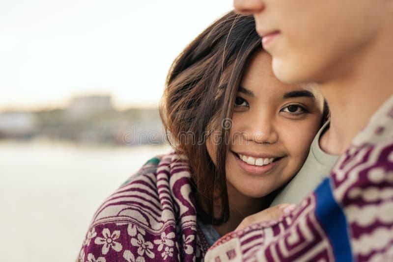 A jovem mulher de sorriso envolveu em uma cobertura com seu noivo foto de stock royalty free