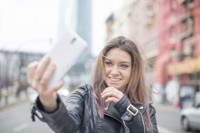 A jovem mulher de sorriso faz o telefone da foto na rua fotos de stock royalty free