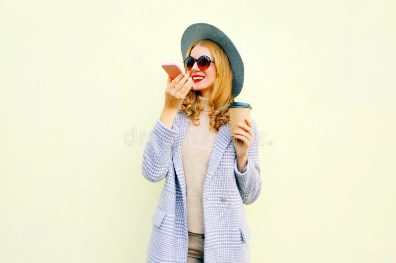 Jovem mulher de sorriso feliz à moda com smartphone usando o registrador do comando da voz ou chamando, revestimento vestindo do  fotografia de stock royalty free