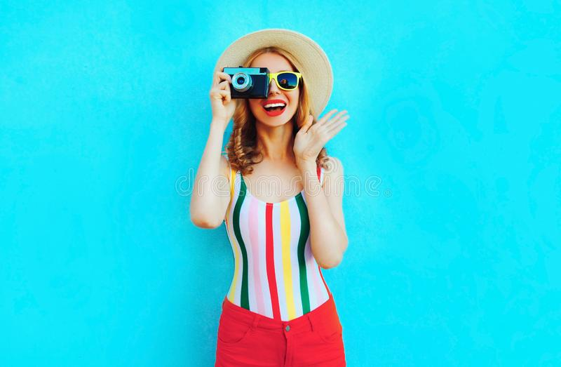 Jovem mulher de sorriso feliz colorida que guarda a câmera retro no chapéu de palha do verão que tem o divertimento em wal azul imagem de stock royalty free