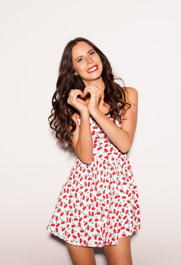 Jovem mulher de sorriso feliz do retrato que mostra o gesto do sinal do coração com nex das mãos ao fundo branco indoor fotos de stock royalty free