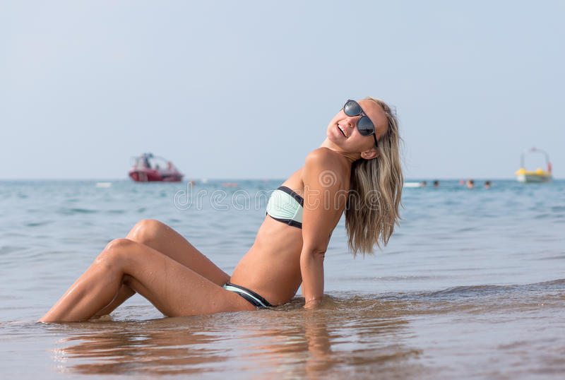 Jovem mulher de sorriso feliz em óculos de sol pretos no mar no tempo do dia Emoções humanas positivas, sentimentos, alegria Mola imagem de stock royalty free